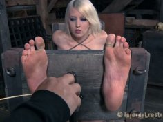 Cherry Torn has her legs and hands locked and feet caned hard